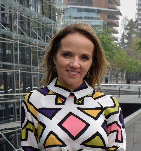 Fotografía de la Doctora Nutrióloga Ada Cuevas usando una chaqueta azul, edificio del Centro Médico CAMMYN en el fondo