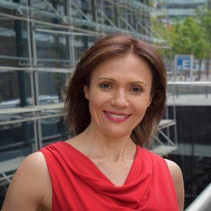 Fotografía de la Doctora Nutrióloga Verónica Álvarez usando una chaqueta azul, edificio del Centro Médico CAMMYN en el fondo