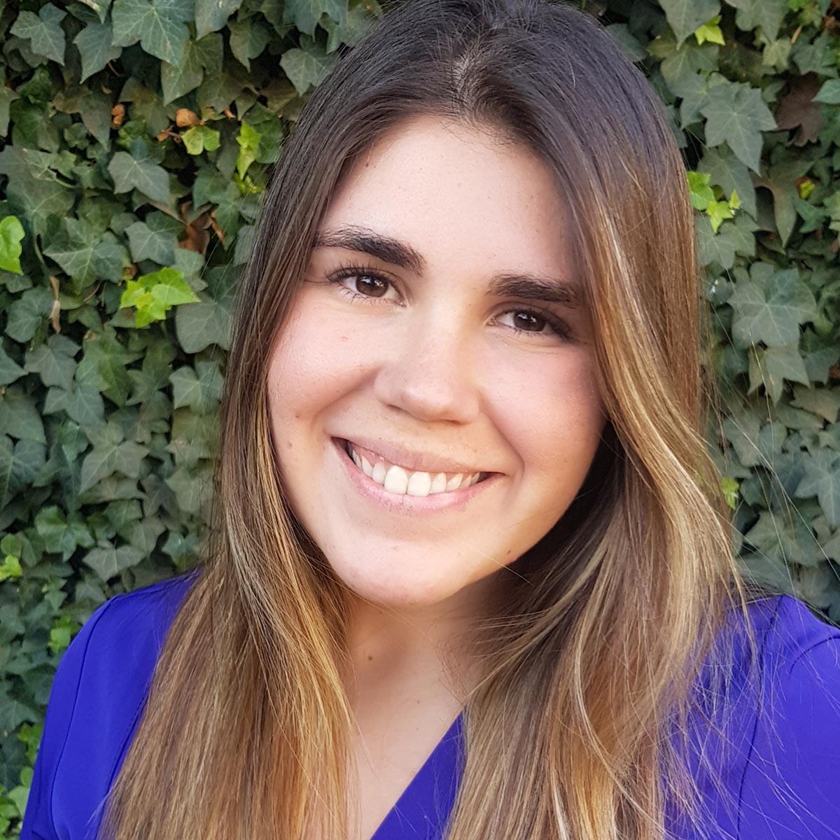 Fotografía de la nutricionista de cammyn, María Jesús Estay. Fondo de ojas verdes